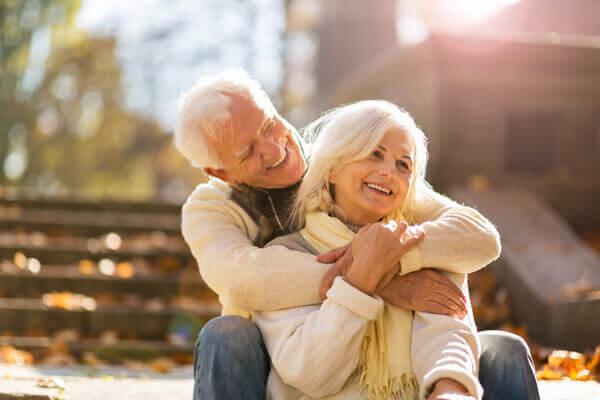 Elderly couple embracing in autumn park
